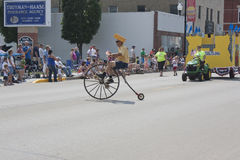 Man with Cheesehead Riding High Wheel Bicycle in parade Royalty Free Stock Image
