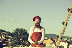 Man chef cooking dough. Man chef cook hipster with long beard on handsome face in red hat and apron cooking dough standing near ladder on blue sky background royalty free stock photos