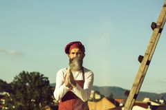 Man chef cooking dough. Man chef cook hipster with long beard on handsome face in red hat and apron cooking dough standing near ladder on blue sky background stock image