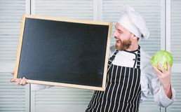 Man chef hat apron hold blackboard copy space. Recipe concept. Cooking delicious meal step by step. Menu for today. List. Ingredients for cooking dish. Check stock photography