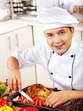 Man in chef hat cooking chicken Stock Photography