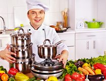 Man in chef hat cooking chicken Royalty Free Stock Image