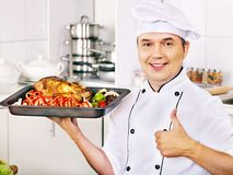 Man in chef hat cooking chicken Stock Image