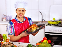 Man in chef hat cooking chicken Royalty Free Stock Images