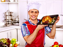 Man in chef hat cooking chicken Stock Photo