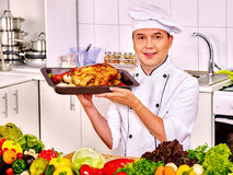 Man in chef hat cooking chicken Royalty Free Stock Photography