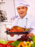 Man in chef hat cooking chicken Stock Images