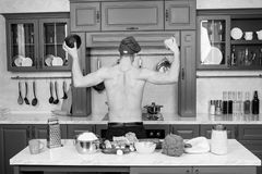 Man in chef hat with muscular torso in kitchen, back view. Cook hold pepper and cabbage in strong hands. Vegetables for. Cooking vegan dishes. Food cooking stock image