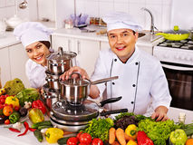 Man in chef hat and woman cooking . Stock Photos