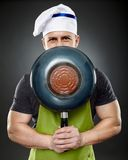 Man chef hiding his face behind a wok pan Stock Photography