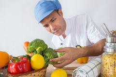 Chef checking. A man of  chef In his kitchen checking vegetable and food for his menu Stock Photo