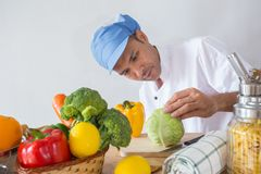 Chef checking. A man of  chef In his kitchen checking vegetable and food for his menu Royalty Free Stock Photos