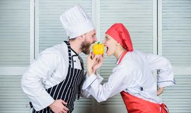 Man chef hold yellow pepper. Just try. Vegetarian family. Woman and bearded man cooking together. Cooking healthy food stock photo