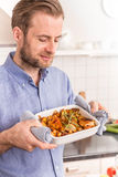 Man or chef holding roasting dish with hot chicken drumsticks Royalty Free Stock Photography