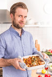 Man or chef holding roasting dish with hot chicken drumsticks Stock Photography