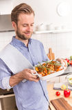 Man or chef holding roasting dish with raw chicken drumsticks Royalty Free Stock Image