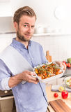 Man or chef holding roasting dish with raw chicken drumsticks Stock Photography