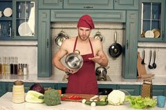 Man chef in apron on bare torso point at saucepan. Man chef in red hat, apron on bare torso point at saucepan at kitchen table. Food, cooking, preparation stock photography
