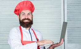 Man chef searching online ingredients cooking food. Grocery shop online. Delivery service. Chef laptop at kitchen. Culinary school. Hipster in hat and apron royalty free stock image