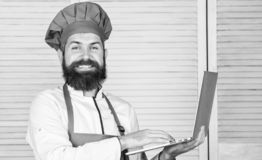 Man chef searching online ingredients cooking food. Grocery shop online. Delivery service. Chef laptop at kitchen. Culinary school. Hipster in hat and apron stock images