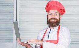 Man chef searching online ingredients cooking food. Grocery shop online. Delivery service. Chef laptop at kitchen. Culinary school. Hipster in hat and apron stock photography
