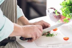A man chef shreds greens at a white table Stock Photo
