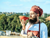 Man chef tasting dish. Young man chef cook with bearded handsome face in red uniform and hat drinking dish from bowl on blue sky green trees and roofs background Stock Photos