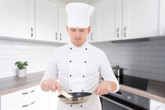 Man chef in uniform holding frying pan in modern kitchen Royalty Free Stock Photography