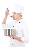 Man in chef uniform tasting something from saucepan isolated on Stock Photo