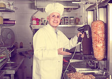 Man chef wearing uniform cutting meat for kebab on kitchen in fa Stock Image