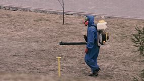 A man in a chemical protection suit and gas mask handles the territory from ticks. A man in a chemical protection suit and gas mask handles the territory from stock video footage