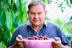 Man with cherries in garden Stock Photo