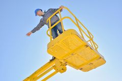 Man in cherry picker bucket pointing into distance. Cherry stock photos
