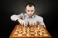 Man at chess board. Chess player at wood chessboard Stock Image