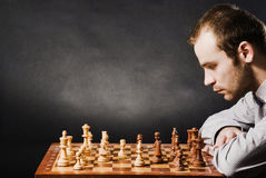Man at chess board. Chess player at wood chessboard Stock Images
