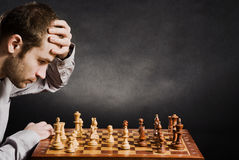 Man at chess board. Chess player at wood chessboard Royalty Free Stock Images