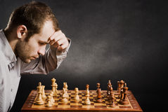 Man at chess board. Chess player at wood chessboard Royalty Free Stock Photography