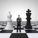 Man on chessboard. Young businessman standing on chessboard with chess Royalty Free Stock Photo