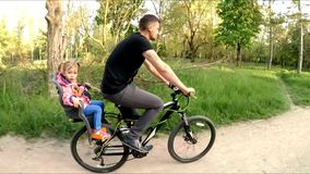 Man With Child On Backseat Riding A Bicycle In stock video footage