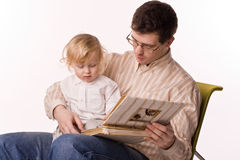Man and child brows a book Stock Photos