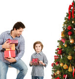 Man and child with Christmas gifts near a Christmas tree. Stock Photos