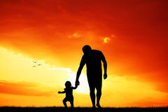 Man and child at dawn Stock Images