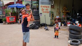 Man with a child in his arms near the tire shop, slums of Asia, residents of poor areas of the royalty free stock images