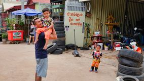 A man with a child in his arms near the tire shop, slums of Asia, residents of poor areas of the. Cambodia, Siem Reap 12/08/2018 a man with a child in his arms stock photos