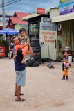 A man with a child in his arms near the tire shop, slums of Asia, residents of poor areas of the royalty free stock photos