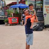 Man with a child in his arms near the tire shop, slums of Asia, residents of poor areas of the stock images