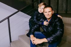 The man with the child in leather jackets. The men with the child in leather jackets sitting on the steps and looking at the camera Stock Photography