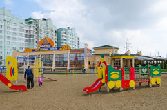 Man with child on modern playground in sleeping district, Gomel. GOMEL, BELARUS - APRIL 14, 2016: Man with child are on modern children`s playground with bright Royalty Free Stock Photos