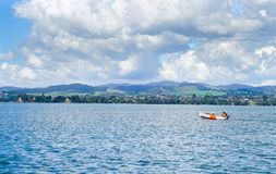 Man and child motoring in small orange and white dinghy. TAURANGA, NEW ZEALAND FEBRUARY 24 2018; Man and child motoring in small orange and white dinghy on Royalty Free Stock Photo
