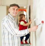 Man with child paints wall Royalty Free Stock Image